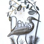 Picture of metal sculpture of a heron walking amongst palmetto and live oak leaves. By Jim Davis