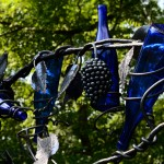Detail picture of metalworked grapes, grapevine with blue bottles by Jim Davis