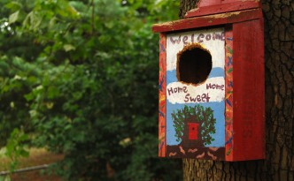Picture of a handpainted birdhouse with the opening enlarged by chewing squirrels.
