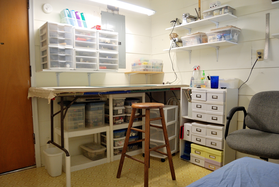 Picture of organized workspace featuring table, stool, shelves and bins and boxes.