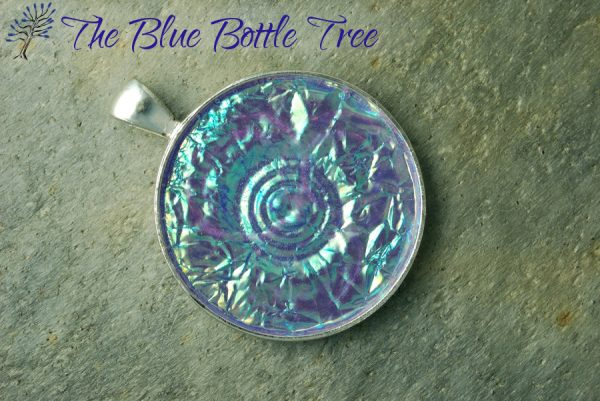 Image of a shiny round blue pendant made from polymer clay with the Holo Effect technique by The Blue Bottle Tree.
