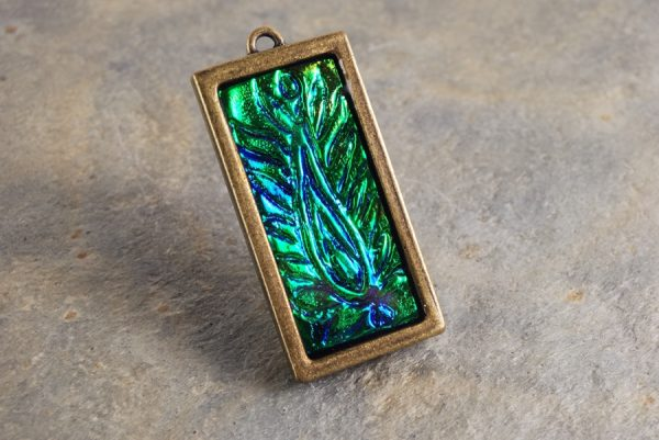 Polymer clay blue flame holographic effect pendant with blue and green.