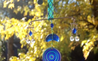 Suncatcher featuring polymer clay, crystals, glass, and beadweaving in blue tones against a fall background.