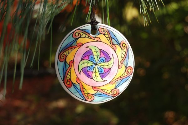 Polymer clay mandala ornament colored with image transfer and colored chalk.