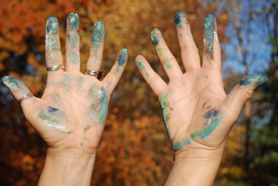 Artist's hands with paint on fingertips.