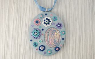 Blue pendant with flowers made from polymer clay and featuring a holographic effect inset.