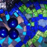 The sun is shining on a mosaic panel made on mirror in colors of cobalt, lime green, and sky blue.