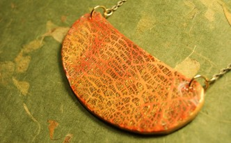 Bib style polymer clay necklace in orange and gold crackle.