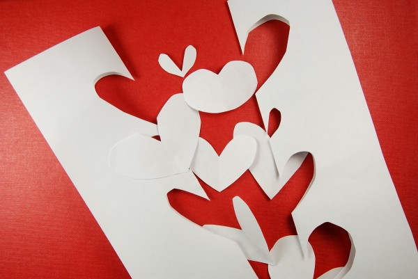 Cut up paper hearts on a red background, badly done.