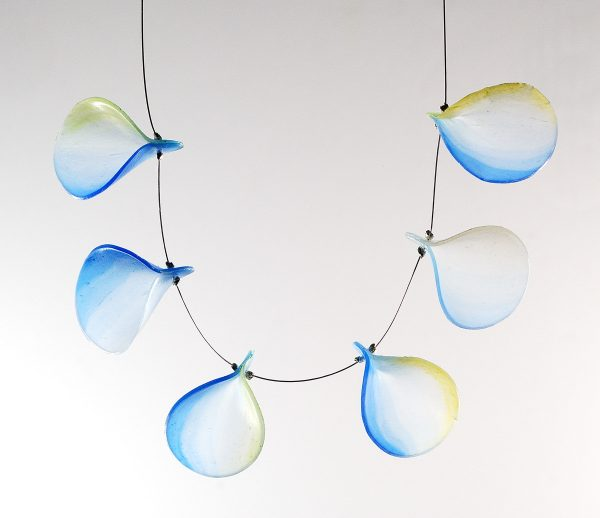 Delicate necklace with flakes of translucent clear plastic arranged on a thin cable. Tinted with alcohol inks and explained in this article.