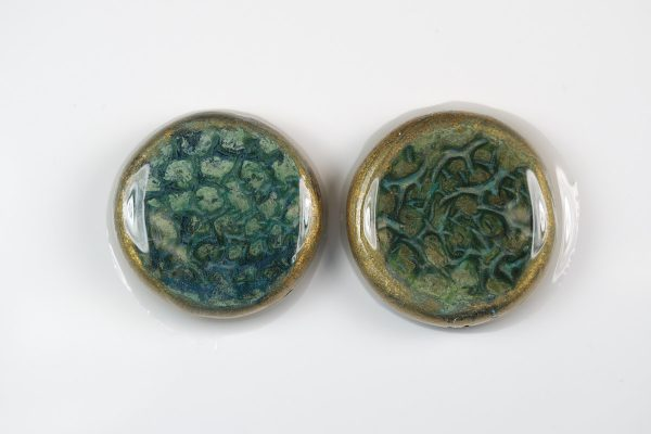 A coating of epoxy resin was used over varathane caused the patina areas to crackle on these polymer clay beads that have been treated with VerDay Paint and Patina. By The Blue Bottle Tree.