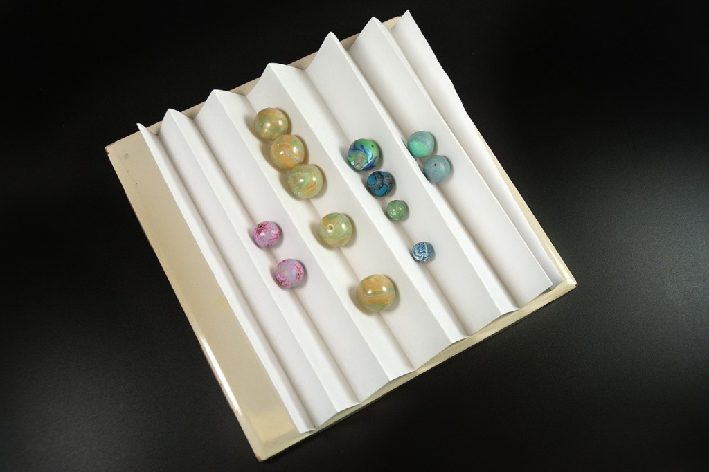 Keep polymer clay beads from rolling around during baking by placing them on accordion folded copy paper.
