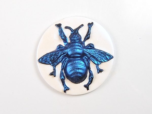 Faux cameo of a polymer clay bee.