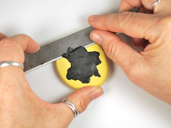 Use a long blade to remove excess polymer clay from the back of a mold.