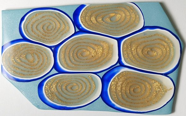 Slices of a translucent spiral cane sliced with the LC Angle Base and cured. Read a review of the LC Slicer and LC Angle Base at The Blue Bottle Tree.