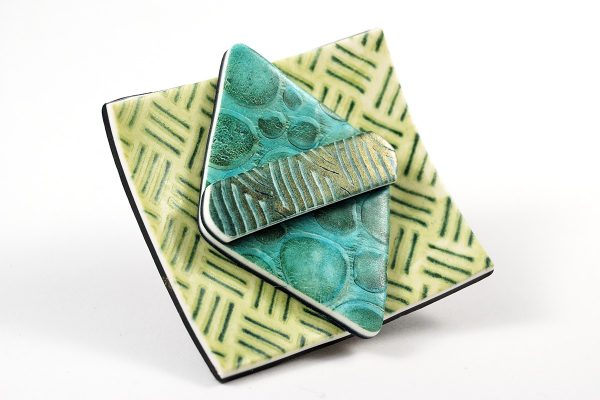 This brooch was created from polymer clay using Kor rollers to create the various textures.