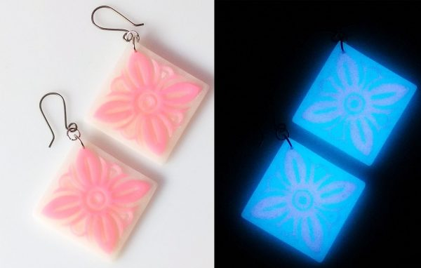 Polymer clay earrings made with the sutton slice technique and glow powders, comparing the light and dark view.